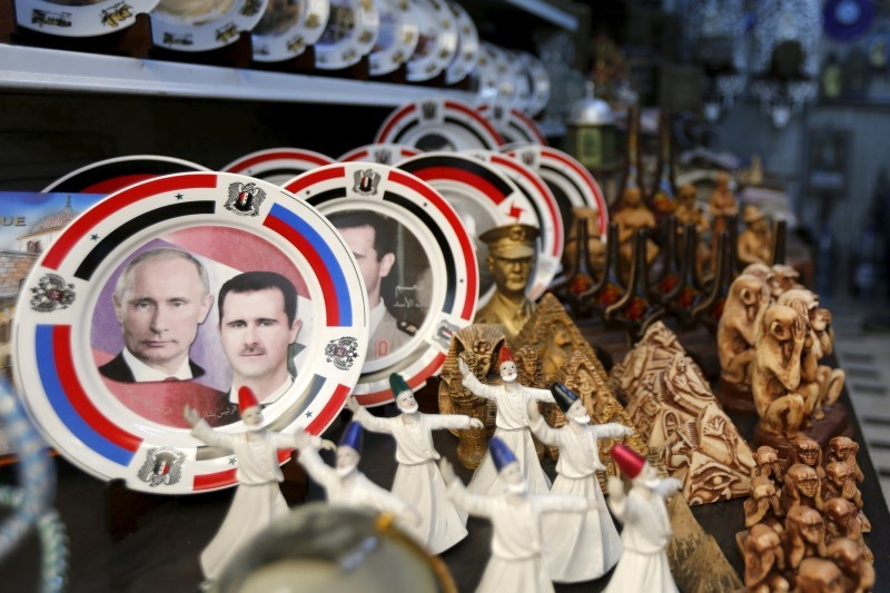 Souvenir plates depicting Syria's President Bashar al-Assad and Russia's President Vladimir Putin are seen among other items for sale in old Damascus, Syria, February 8, 2016. REUTERS/Omar Sanadiki