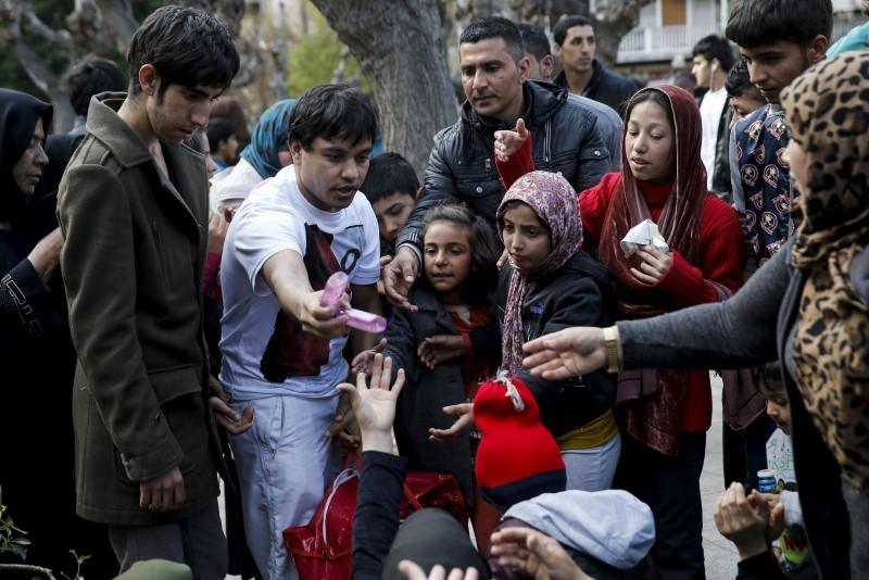 A volunteer (2nd L) gives away goods to stranded refugees and migrants, most of them Afghans, who find shelter on Victoria Square in Athens, Greece, March 3, 2016. REUTERS/Alkis Konstantinidis