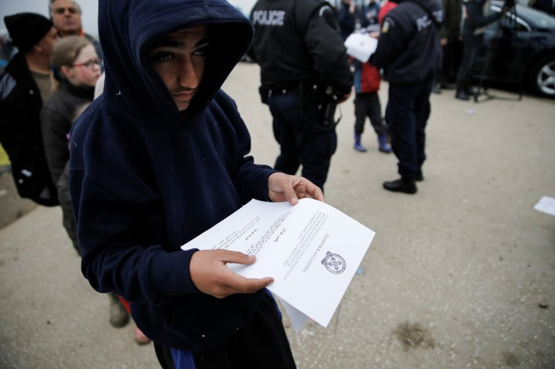 A boy reads an announcement distributed by Greek police officers informing refugees and migrants that the borders to Macedonia are closed and they should consider moving to relocation centers, at a makeshift camp at the Greek-Macedonian border near the village of Idomeni, Greece, March 18, 2016. REUTERS/Alkis Konstantinidis