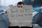 """A refugee holds a message, """"Thank you EU for closing the border"""" during a protest asking for the opening of borders at a makeshift camp at the Greek-Macedonian border near the village of Idomeni, Greece, March 18, 2016. REUTERS/Alkis Konstantinidis"""