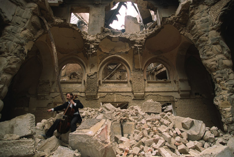 A cello player in Sarajevo's destroyed National Library, 1992. Photo by Mikhail Evstafiev, Creative Commons