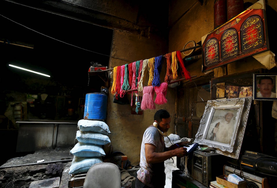 "Hisham Aly, 37, takes an order on the phone at a dye workshop in old Cairo, Egypt, March 17, 2016. Egypt's hard currency crisis and competition from modern factories in Asia and at home threaten one of the last dye workshops in Egypt. But one of its owners takes comfort in the trade's ancient resilience. Mohamed Mostafa boasts that the profession dates back 3,000 years, so it can survive anything. REUTERS/Amr Abdallah Dalsh SEARCH ""AMR DYE"" FOR THIS STORY. SEARCH ""THE WIDER IMAGE"" FOR ALL STORIES"