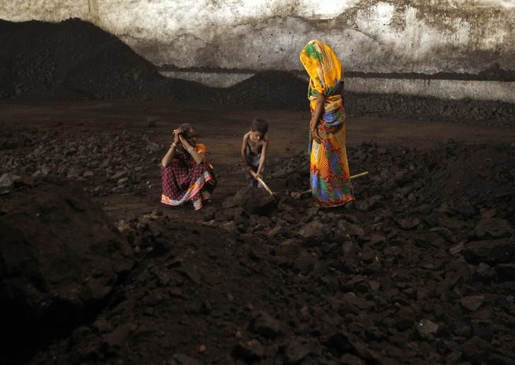 Labourers rest as a boy playfully shovels coal at a yard in the western Indian city of Ahmedabad November 20, 2014. India will allow locally registered foreign firms to mine and sell coal when commercial mining is permitted as part of the opening up of the nationalised industry after four decades, Coal Secretary Anil Swarup told Reuters. To match Interview INDIA-COAL/ REUTERS/Amit Dave