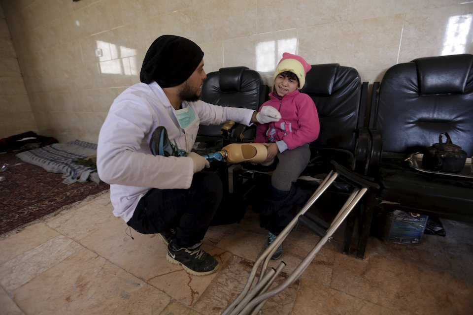 "Khamis (L), 24, fits an artificial limb on nine-year-old Salma's amputated leg in the rebel-controlled area of Maaret al-Numan town in Idlib province, Syria March 20, 2016. Two university students forced to interrupt their studies have learnt to make and fit hundreds of new limbs in the past four years in opposition-held areas of Syria. A mobile clinic operating from a truck has gone some way to improve access to treatment. While most patients are between 15 and 45, the clinic also helps children and the elderly with replacement limbs. REUTERS/Khalil Ashawi SEARCH ""SYRIA AMPUTEE"" FOR THIS STORY. SEARCH ""THE WIDER IMAGE"" FOR ALL STORIES"