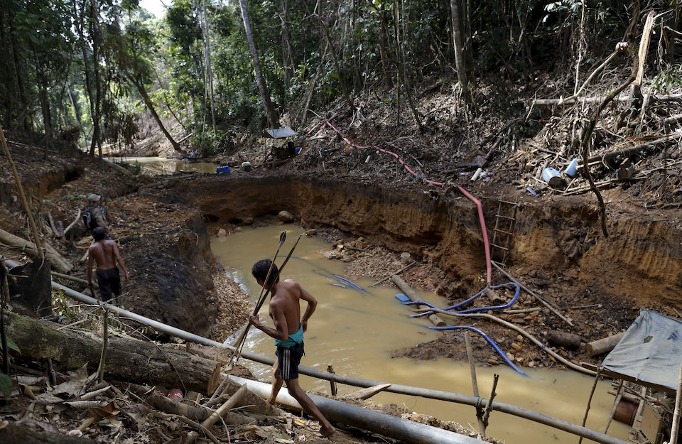 Yanomami indians follow agents of Brazil's environmental agency in an illegal gold mine during an operation against illegal gold mining on indigenous land, in the heart of the Amazon rainforest, in Roraima state, Brazil April 17, 2016. At over 9.5 million hectares, the Yanomami territory is twice the size of Switzerland and home to around 27,000 indians. The land has legally belonged to the Yanomami since 1992, but illegal miners continue to plague the area, sawing down trees and poisoning rivers with mercury in their lust for gold. REUTERS/Bruno Kelly