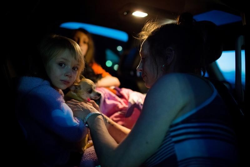 Fort McMurray resident Crystal Maltais buckles in her daughter, Mckennah Stapley, as they prepare to leave Conklin, Alberta, for Lac La Biche after evacuating their home in Fort McMurray on Tuesday May 3, 2016. REUTERS/Topher Seguin
