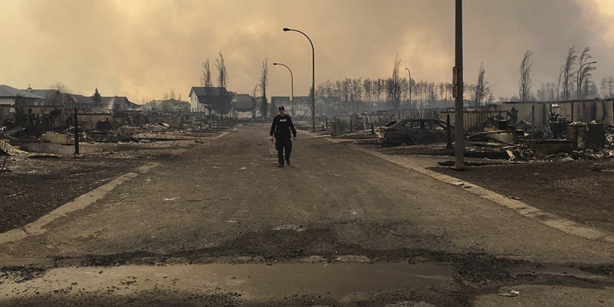 A Mountie surveys the damage on a street in Fort McMurray, Alberta, Canada in this May 4, 2016 image posted on social media. Courtesy Alberta RCMP/Handout via REUTERS