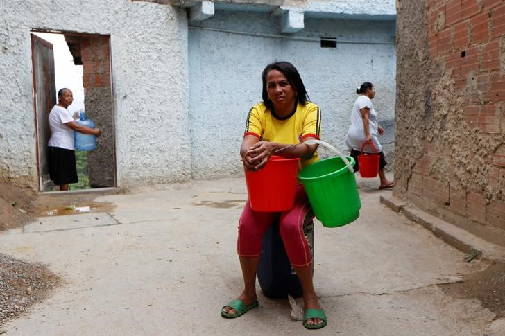 "Maria Rivero, carrying plastic containers used to carry water, poses for a picture in a neighbourhood called ""The Tank"" at the slum of Petare in Caracas, Venezuela, April 3, 2016. Although their nation has one of the world's biggest hydroelectric dams and vast rivers like the fabled Orinoco, Venezuelans are still suffering water and power cuts most days. The problems with stuttering services have escalated in the last few weeks: yet another headache for the OPEC nation's 30 million people already reeling from recession, the world's highest inflation rate, and scarcities of basic goods. President Nicolas Maduro blames a drought, while the opposition blames government incompetence. REUTERS/Carlos Garcia Rawlins SEARCH ""SERVICES TANK"" FOR THIS STORY. SEARCH ""THE WIDER IMAGE"" FOR ALL STORIES"