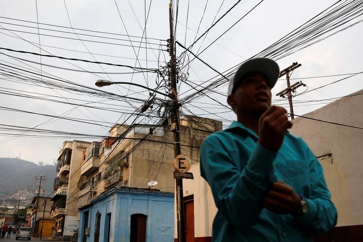 "A man walks past an electric pole with overhead power cables in Caracas, Venezuela, April 2, 2016. Although their nation has one of the world's biggest hydroelectric dams and vast rivers like the fabled Orinoco, Venezuelans are still suffering water and power cuts most days. The problems with stuttering services have escalated in the last few weeks: yet another headache for the OPEC nation's 30 million people already reeling from recession, the world's highest inflation rate, and scarcities of basic goods. President Nicolas Maduro blames a drought, while the opposition blames government incompetence. REUTERS/Carlos Garcia Rawlins SEARCH ""SERVICES TANK"" FOR THIS STORY. SEARCH ""THE WIDER IMAGE"" FOR ALL STORIES"