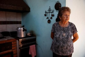 "Arcelia Leandro poses for a picture at the kitchen of her house, while she waits for the power to return, during a power cut in Puerto Ordaz in Bolivar state, Venezuela, April 12, 2016. Although their nation has one of the world's biggest hydroelectric dams and vast rivers like the fabled Orinoco, Venezuelans are still suffering water and power cuts most days. The problems with stuttering services have escalated in the last few weeks: yet another headache for the OPEC nation's 30 million people already reeling from recession, the world's highest inflation rate, and scarcities of basic goods. President Nicolas Maduro blames a drought, while the opposition blames government incompetence. REUTERS/Carlos Garcia Rawlins SEARCH ""SERVICES TANK"" FOR THIS STORY. SEARCH ""THE WIDER IMAGE"" FOR ALL STORIES"
