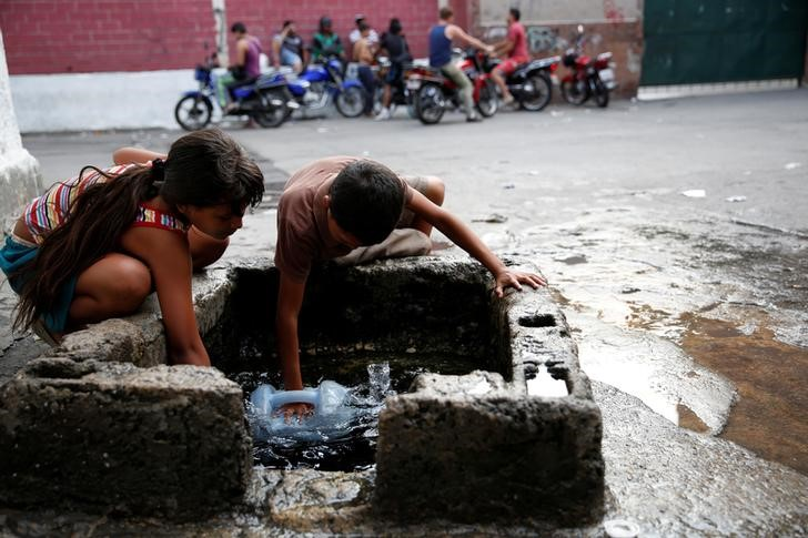 "Children fill plastic containers with water from a well on a street, close to a neighbourhood called ""The Tank"" in the slum of Petare in Caracas, Venezuela, March 17, 2016. Although their nation has one of the world's biggest hydroelectric dams and vast rivers like the fabled Orinoco, Venezuelans are still suffering water and power cuts most days. The problems with stuttering services have escalated in the last few weeks: yet another headache for the OPEC nation's 30 million people already reeling from recession, the world's highest inflation rate, and scarcities of basic goods. President Nicolas Maduro blames a drought, while the opposition blames government incompetence. REUTERS/Carlos Garcia Rawlins SEARCH ""SERVICES TANK"" FOR THIS STORY. SEARCH ""THE WIDER IMAGE"" FOR ALL STORIES"