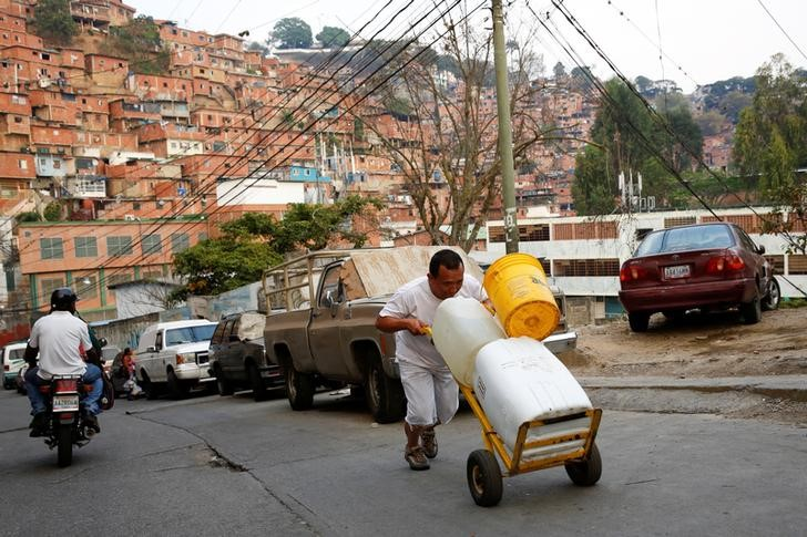 "A man pushes a wheelbarrow loaded with water containers in a neighbourhood called ""The Tank"" at the slum of Petare in Caracas, Venezuela, March 17, 2016. Although their nation has one of the world's biggest hydroelectric dams and vast rivers like the fabled Orinoco, Venezuelans are still suffering water and power cuts most days. The problems with stuttering services have escalated in the last few weeks: yet another headache for the OPEC nation's 30 million people already reeling from recession, the world's highest inflation rate, and scarcities of basic goods. President Nicolas Maduro blames a drought, while the opposition blames government incompetence. REUTERS/Carlos Garcia Rawlins SEARCH ""SERVICES TANK"" FOR THIS STORY. SEARCH ""THE WIDER IMAGE"" FOR ALL STORIES"
