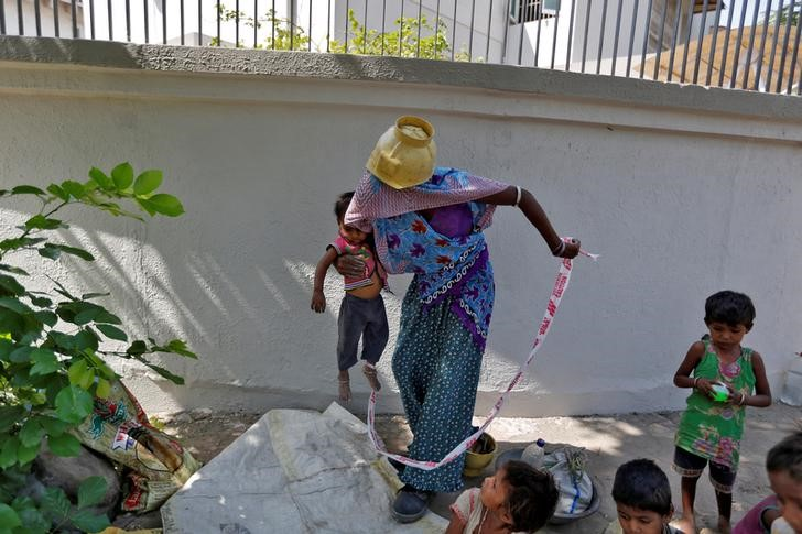 Sarta Kalara, a construction worker, holds her 15-month-old Shivani as a barrier tape is tied to Shivani's ankle to prevent her from running away when Kalara works nearby in Ahmedabad, India, April 20, 2016. Kalara says she has no option but to tether her daughter Shivani to a stone despite her crying, while she and her husband work for 250 rupees ($3.8) each a shift digging holes for electricity cables in the city of Ahmedabad. There are about 40 million construction workers in India, at least one in five of them women, and the majority poor migrants who shift from site to site, building infrastructure for India's booming cities. Across the country it is not uncommon to see young children rolling in the sand and mud as their parents carry bricks or dig for new roads or luxury houses. REUTERS/Amit Dave