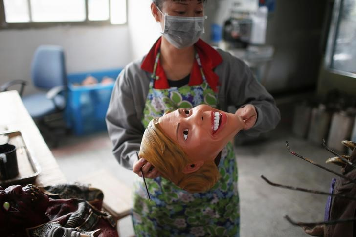 A worker checks a mask of U.S. Democratic presidential candidate Hillary Clinton, which she just painted, at Jinhua Partytime Latex Art and Crafts Factory in Jinhua, Zhejiang Province, China, May 25, 2016. REUTERS/Aly Song