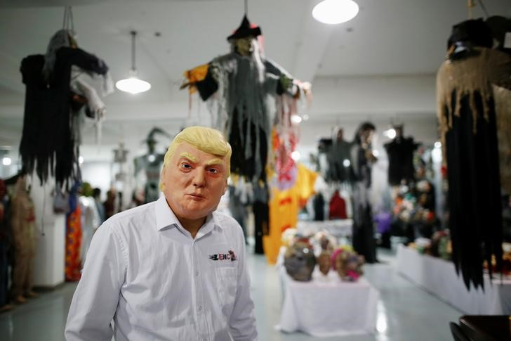 The manager of Jinhua Partytime Latex Art and Crafts Factory wearing a mask of U.S. Republican presidential candidate Donald Trump poses as he presents products to reporters at his factory's showroom in Jinhua, Zhejiang Province, China, May 25, 2016. REUTERS/Aly Song