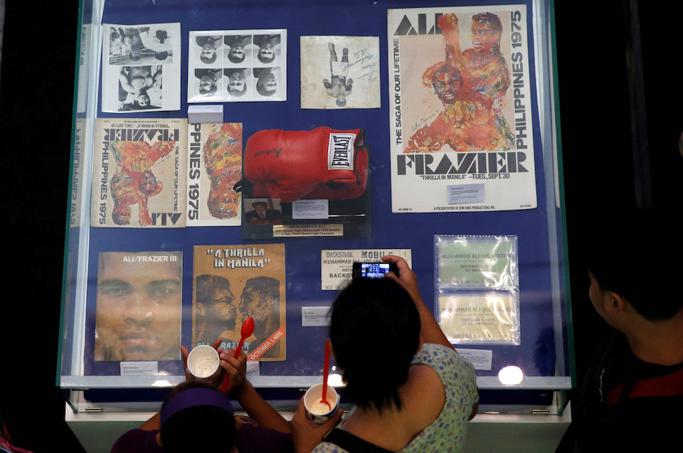 "A fan uses a mobile phone to take pictures of late boxer Muhammad Ali's memorabilias of the 1970 bout with Joe Frazier, dubbed as ""Thrilla in Manila"" in Cubao Quezon City, Metro Manila, Philippines June 10, 2016.   REUTERS/Erik De Castro"