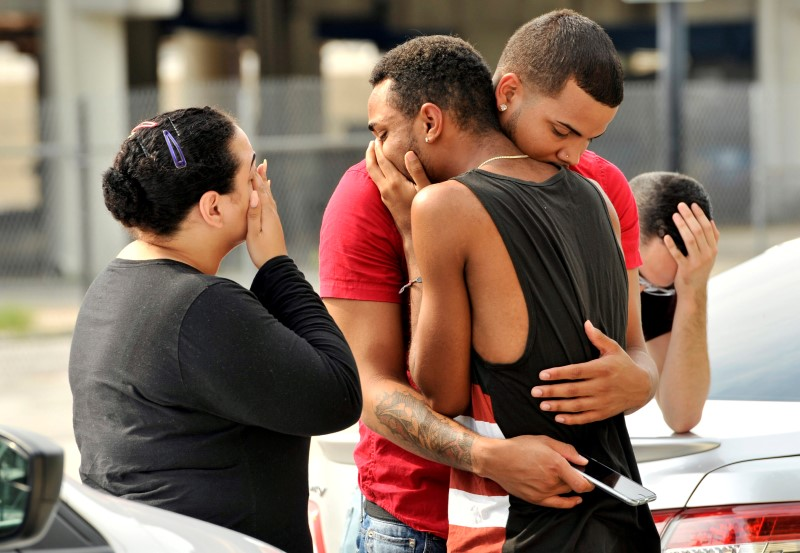 Friends and family members embrace outside the Orlando Police Headquarters during the investigation of a shooting at the Pulse night club,in Orlando, Florida, June 12, 2016. REUTERS/Steve Nesius