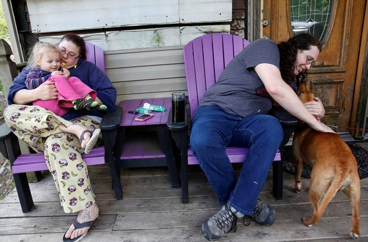 Kate Lynn Blatt (R), a transgender woman, pets her dog as her sister Tracy sits with her granddaughter Gabriella King, 3, on the porch of Kate's home in Pottsville, Pennsylvania, United States, May 24, 2016.  REUTERS/Shannon Stapleton