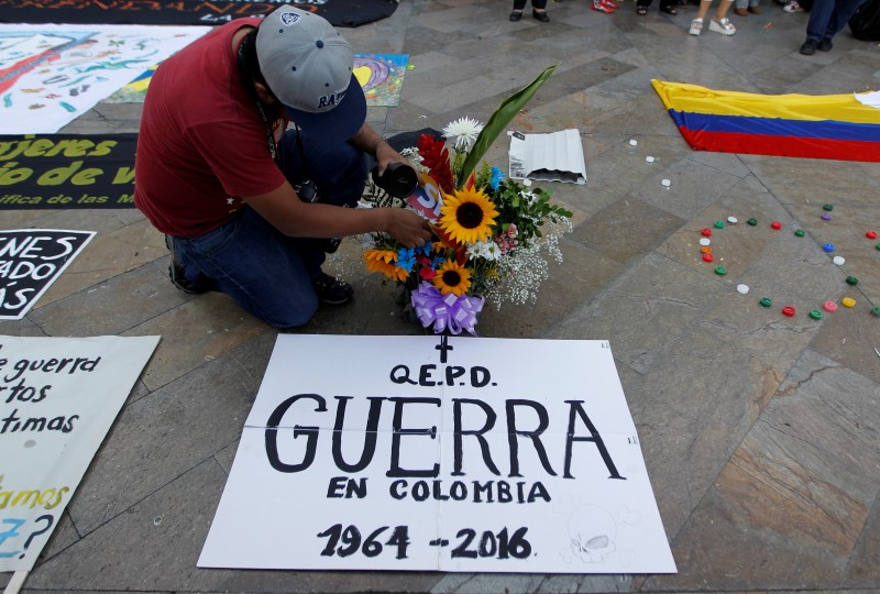 "A man celebrates the signing of a historic ceasefire deal between the Colombian government and FARC rebels at Botero square in Medellin, Colombia, June 23, 2016. The sign reads ""RIP the War in Colombia 1964 - 2016"".  REUTERS/Fredy Builes"
