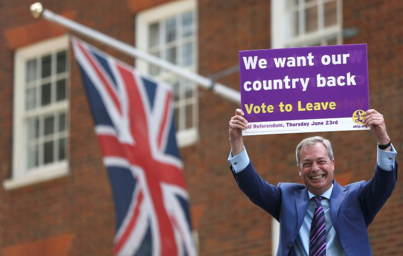Leader of the United Kingdom Independence Party Nigel Farage holds a placard as he launches his party's EU referendum tour bus in London, Britain May 20, 2016. REUTERS/Neil Hall