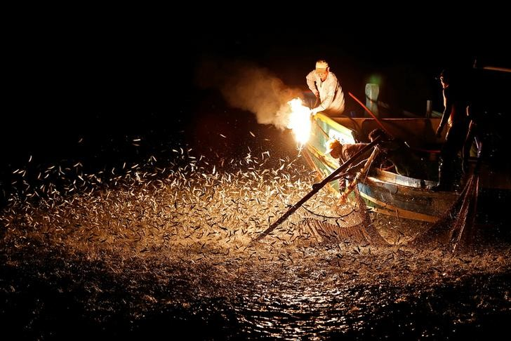 "Fishermen use a fire to attract fish on a traditional ""sulfuric fire fishing"" boat in New Taipei City, Taiwan June 19, 2016. REUTERS/Tyrone Siu"