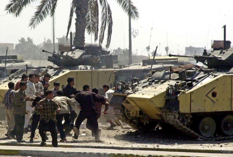 Youths hurls rock at British Army Warrior armoured vehicles during a violent protest by job seekers, who say they were promised employment in the security services, in the southern Iraq city of Basra March 22, 2004. REUTERS/Atef Hassan/File Photo