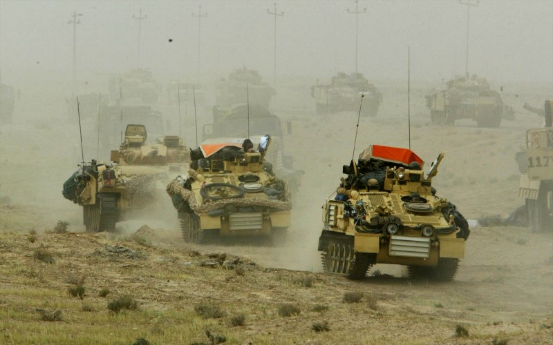 A British army armoured vehicle convoy rolls into southern Iraq March 22, 2003. REUTERS/Oleg Popov/File Photo