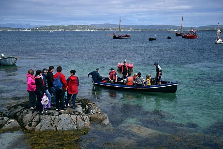 People wait on a rock to be brought back to Carna by local fishermen off the coast of Galway, Ireland, July 16, 2016. Seafarers and other members of the Carna community make an annual pilgrimage to MacDara's Island, home to a 6th Century oratory, to attend a mass for St. MacDara, the patron saint of fishermen. The pilgrimage is believed to keep seafarers safe throughout the year. REUTERS/Clodagh Kilcoyne ?
