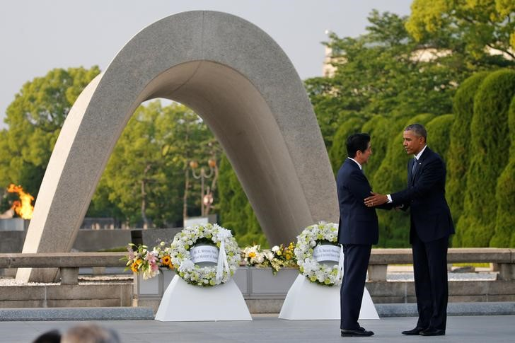 U.S. President Barack Obama (R) puts his arm around Japanese Prime Minister Shinzo Abe after they laid wreaths in front of a cenotaph at Hiroshima Peace Memorial Park in Hiroshima, Japan May 27, 2016. REUTERS/Carlos Barria