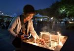 A woman lights up a candle in front of the cenotaph for the victims of the 1945 atomic bombing at Peace Memorial Park in Hiroshima, western Japan, in this photo taken by Kyodo August 6, 2016. Mandatory credit Kyodo/via REUTERS