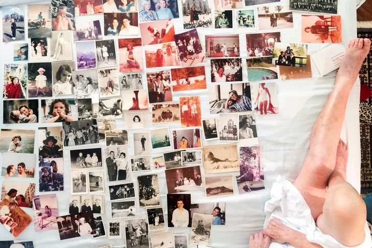 Old family photographs are seen on Marisa VescoÕs bed as she works on creating a family album with her granddaughter, the photographer Gaia Squarci in Cossato, Italy, July 1, 2015. REUTERS/Gaia Squarci