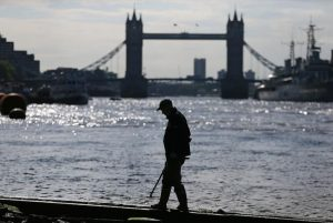 Mudlark Matthew Goode uses a metal detector to look for objects near Tower Bridge on the bank of the River Thames in London, Britain May 23, 2016. REUTERS/Neil Hall