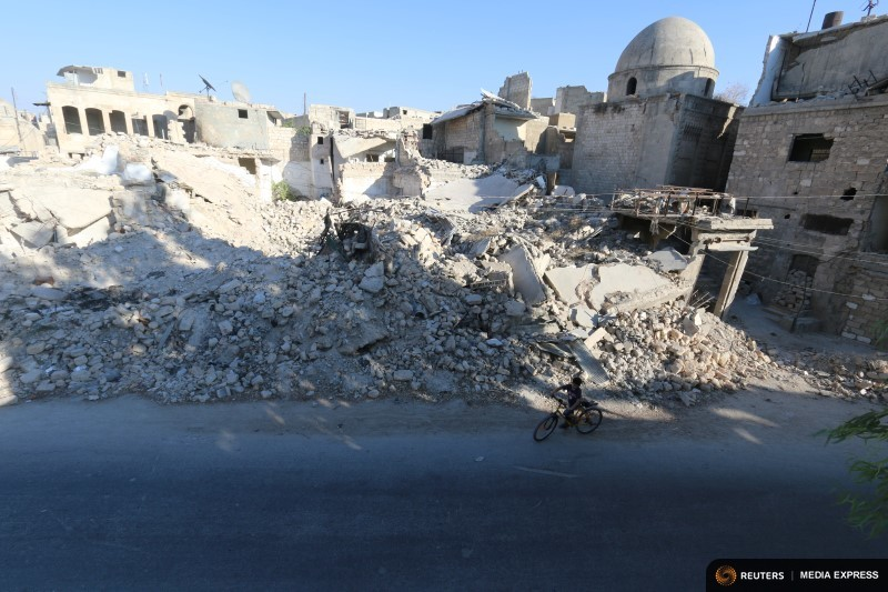 A boy rides a bicycle near rubble of damaged buildings in the rebel held al-Maadi district of Aleppo, Syria, August 31, 2016. REUTERS/Abdalrhman Ismail