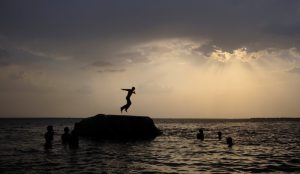 A boy prepares to jump off a rock into the waters of the Osman Sagar Lake near the southern Indian city of Hyderabad May 29, 2011. REUTERS/Krishnendu Halder/File Photo