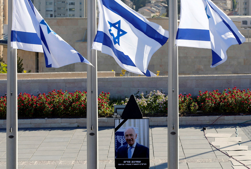 A portrait of former Israeli President Shimon Peres is seen near Israeli flags lowered to half mast at the Knesset plaza, the Israeli parliament, ahead of his funeral, in Jerusalem September 30, 2016. REUTERS/Ammar Awad
