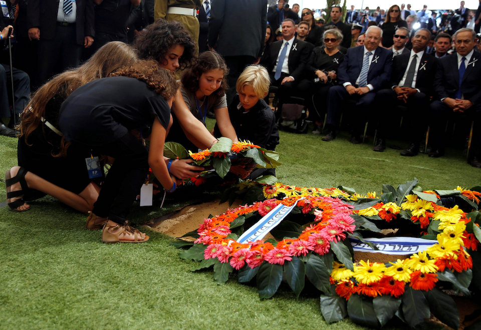 Grandchildren of former Israeli President Shimon Peres lay a wreath on the grave of their grandfather during the burial ceremony at Mount Herzl Cemetery in Jerusalem September 30, 2016. REUTERS/Ronen Zvulun