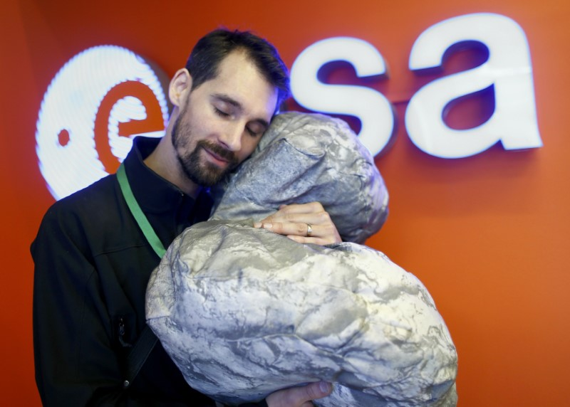 European Space Agency's (ESA) staff Mattial Malmer poses with a comet 67P/ Churyumov-Gerasimenko shape pillow at the European Space Agency's (ESA) headquarters in Darmstadt, Germany, September 30, 2016, as the the Rosetta spacecraft is nearing the end of its historic, 12-year comet chase.      REUTERS/Ralph Orlowski