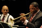 Wynton Marsalis, with long time ensemble member, drummer Ali Jackson, in the background. Frank Stewart, publicity photo