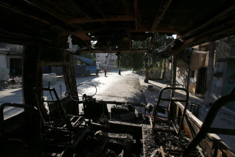 People walk past a burnt bus in the rebel held Seif al-Dawla neighbourhood of Aleppo, Syria October 6, 2016. REUTERS/Abdalrhman Ismail