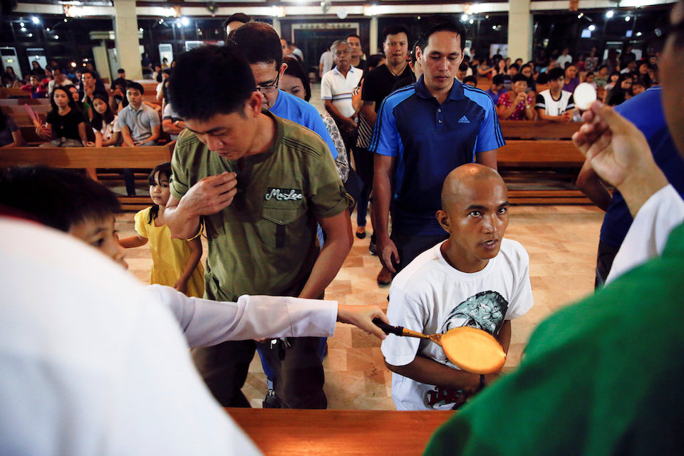 Believers receive communion during a service in a chapel at Camp Crame, the headquarters of Philippine National Police (PNP) in Manila, Philippines October 9, 2016. REUTERS/Damir Sagolj