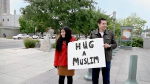 """Negin Farsad and Dean Obeidallah, co-producers of The Muslims are Coming!, hold up a """"Hug a Muslim"""" sign in Salt Lake City, in a still from their 2012 film. Publicity photo"""