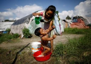 A girl showers her sister at the displacement camp for earthquake victims at Chuchepati in Kathmandu, Nepal, September 19, 2016. Picture taken September 19, 2016. To match Insight NEPAL-QUAKE/POLITICS Thomson Reuters Foundation/Navesh Chitrakar  - RTST7C9
