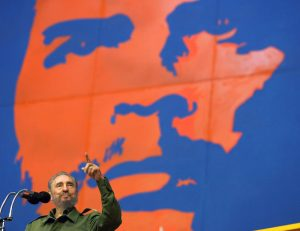 Then Cuban President Fidel Castro acknowledges the applause of the audience while standing underneath an image of late revolutionary hero Ernesto Che Guevara, during the inauguration of games involving mainly Cuban and Venezuelan athletes in Havana in this June 17, 2005 file photo. REUTERS/Claudia Daut/File Photo