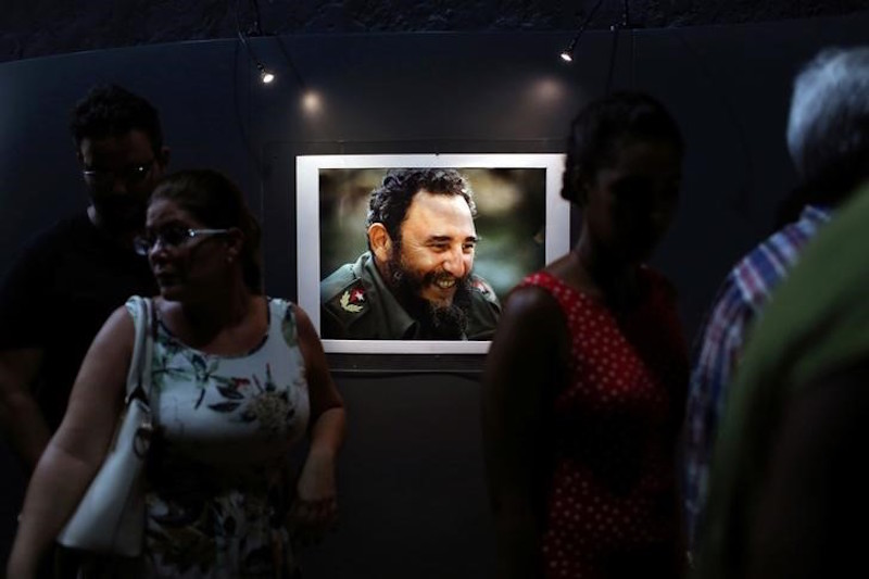 "Fidel Castro is dead, age 90. Read our report, fact box, and analysis. Above, People look at a picture of Cuba's former President Fidel Castro during the opening of the exhibition ""Fidel"" in Havana, Cuba, August 12, 2016.  REUTERS/Alexandre Meneghini"