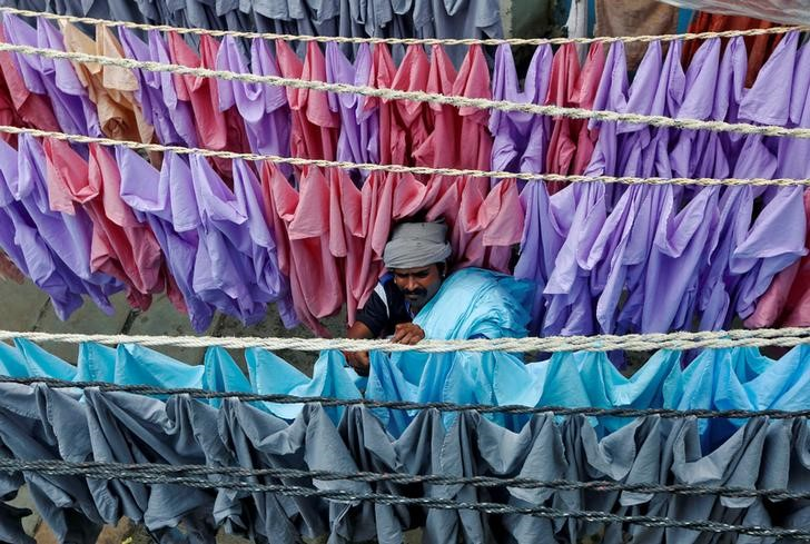 A man hangs shirts out to dry in an open-air laundry in Mumbai, India August 30, 2016. REUTERS/Shailesh Andrade/File Photo GLOBAL BUSINESS WEEK AHEAD PACKAGE Ð SEARCH ÒBUSINESS WEEK AHEAD SEPTEMBER 12Ó FOR ALL IMAGES - RTSNAG5