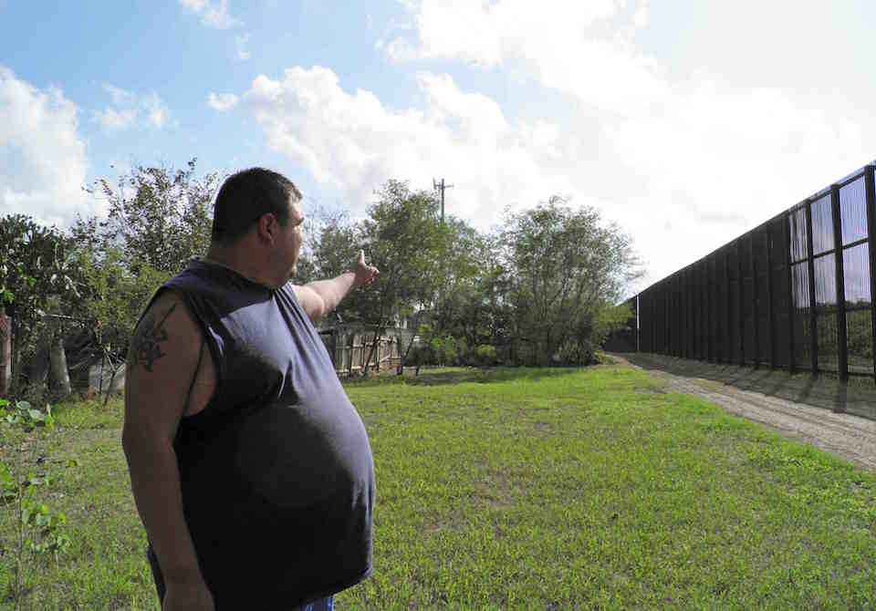 Ernest Villarreal points to where the U.S. border fence passes through the backyard of his family's home in Brownsville, Texas, U.S. on November 18, 2016.     REUTERS/Jon Herskovitz