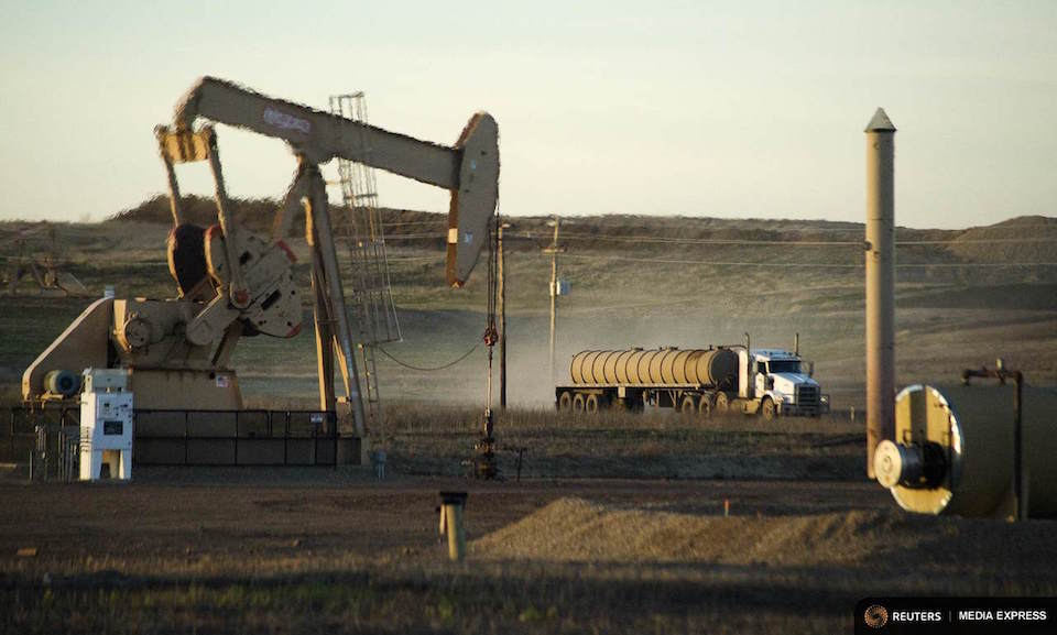 A service truck drives past an oil well on the Fort Berthold Indian Reservation in North Dakota, U.S. on November 1, 2014.  REUTERS/Andrew Cullen/File Photo