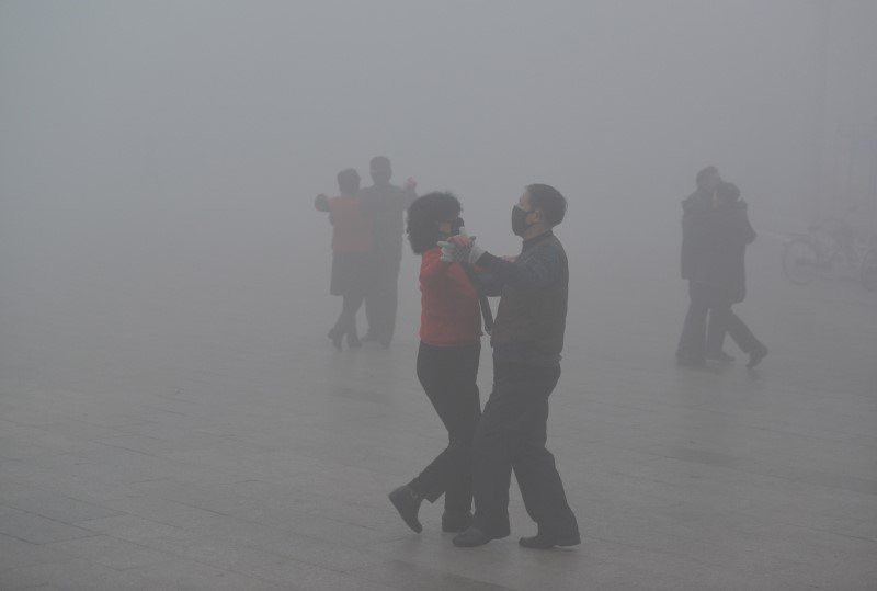 People wearing masks dance at a square among heavy smog during a polluted day in Fuyang, Anhui province, China, January 3, 2017. China Daily/via REUTERS