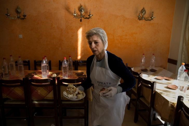 Retired teacher and volunteer Eva Agkisalaki clears tables at a soup kitchen run by the Orthodox church in Athens, Greece, February 15, 2017. REUTERS/Alkis Konstantinidis