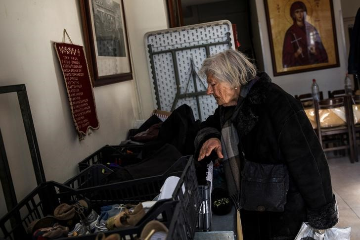"An elderly woman searches through donated clothes at a soup kitchen run by the Orthodox church in Athens, Greece, February 15, 2017. REUTERS/Alkis Konstantinidis             SEARCH ""POVERTY GREECE"" FOR THIS STORY. SEARCH ""WIDER IMAGE"" FOR ALL STORIES."